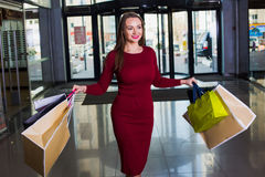 Portrait of beautiful happy  welldressed  woman with shopping bags. Shopping center. Successful shopping day Stock Photos