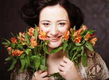 Young attractive young girl holds the bouquet of red and yellow. Portrait of beautiful happy woman with flowers in hands. Young attractive young girl holds the Stock Photos