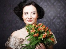 Young attractive young girl holds the bouquet of red and yellow. Portrait of beautiful happy woman with flowers in hands. Young attractive young girl holds the Stock Photography