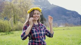 Portrait of beautiful happy woman trying dandelion wreath on mountains backdrop. 4k stock footage