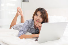 Portrait of beautiful happy young asian woman Working on the bed stock images