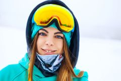 Happy young snowboarder girl in snowboard goggles. Royalty Free Stock Images
