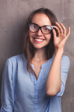 Portrait of beautiful happy young woman with glasses near grey background wall Royalty Free Stock Photos