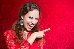 Portrait of a beautiful happy young woman pointing finger at  Royalty Free Stock Photos