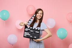 Portrait of beautiful happy young woman wearing blue dress holding classic black film making clapperboard on pink stock image