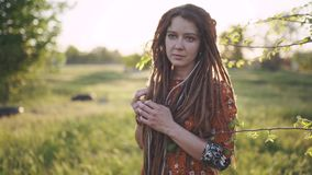 Portrait of an beautiful hippie woman with dreadlocks in the woods at sunset having good time outdoors