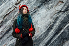 Portrait of a beautiful hipster girl on the background  the rocky cliffs. Dyed hair, blue, long. Royalty Free Stock Photo