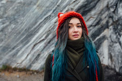 Portrait of a beautiful hipster girl on the background  the rocky cliffs. Dyed hair, blue, long. Stock Images