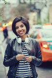 Portrait of beautiful Hispanic latin girl woman short black hair in leather jacket with headphones outside