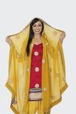 Portrait of beautiful Indian woman in salwar kameez standing over gray background Stock Photo