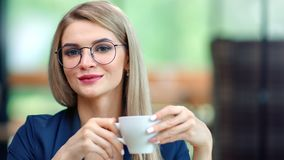 Portrait of beautiful informal business woman in stylish glasses smiling drinking coffee from cup. Portrait of beautiful informal business woman in stylish stock video footage