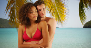 Portrait of beautiful interracial couple hugging each other under palm tree. Royalty Free Stock Images