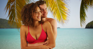 Portrait of beautiful interracial couple hugging each other under palm tree. Stock Image