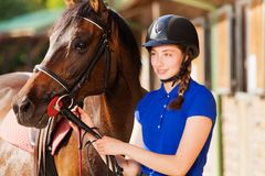 Beautiful jockey girl with her purebred bay horse Royalty Free Stock Images
