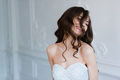 Portrait of beautiful joyful smiling curly bride, with fingers in her hair. Wedding hairstyle and make-up. Stock Images