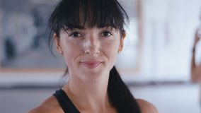 Portrait of beautiful woman fighter looking confident at camera. Attractive sportswoman after training in fitness gym. Portrait of beautiful kickboxing woman stock video footage