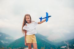 Beautiful happy little girl in mountains in the background of fog stock image