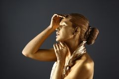 Portrait of beautiful lady with gold paint on skin stock images
