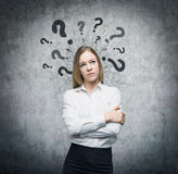A portrait of a beautiful lady with questioning expression and question marks above her head. Royalty Free Stock Photography