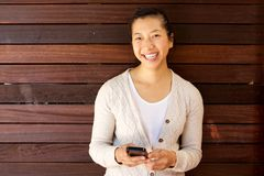 Beautiful lady smiling with mobile phone against a wooden wall Royalty Free Stock Photography