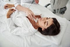 Young woman lying on daybed during medical examination stock image