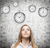 A portrait of a beautiful lady who is looking at the hovering pocket watches. A concept of a value of time in business. Business i. Cons are drawn over the Royalty Free Stock Images