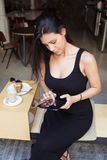 Portrait of a beautiful latin woman reading digital e-book on touch pad while sitting in cafe in the fresh air during coffee break Stock Images