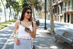Portrait of a beautiful Latin woman with trendy look using cell telephone while walking outside in summer day Royalty Free Stock Image