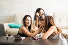 Friends helping put some makeup on. Portrait of a beautiful Latin young women putting makeup on a friend while they get ready to go out together Royalty Free Stock Image
