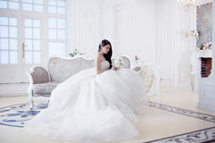 Portrait of beautiful laughing bride. Wedding dress with open back. Luxurious light interior stock images