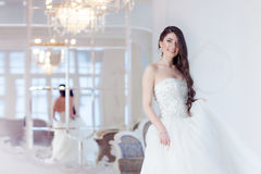 Portrait of beautiful laughing bride. Wedding dress with open back. Luxurious light interior royalty free stock image