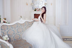 Portrait of beautiful laughing bride. Wedding dress with open back. Luxurious light interior royalty free stock images