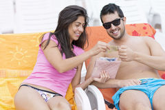 Portrait of beautiful laughing couple with money in the hands. Portrait of a beautiful brunette women with money  in the hands laying on the beach with his Stock Photo