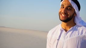 Portrait of beautiful laughing emirate male in sandy desert against blue sky outdoors. Close-up shot of portrait of Arabian Sheikh young man with beautiful smile stock video footage