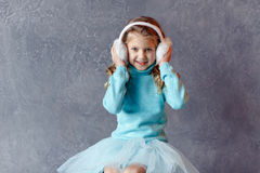Portrait of beautiful laughing girl in a blue skirt and fur head Stock Photography