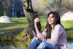 Portrait of beautiful laughing woman counting money in the park Royalty Free Stock Images