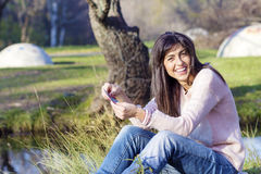 Portrait of beautiful laughing woman counting money in the park Stock Photography
