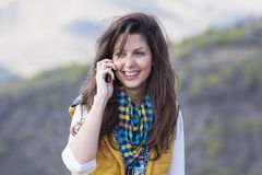 Portrait of beautiful laughing woman talking on the phone outdoor Stock Photography
