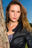 Portrait of a beautiful leaning against a tree trunk Royalty Free Stock Photography