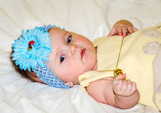 Portrait of a beautiful little baby girl in a yellow dress with a bow on her head that plays beads jewelry around his neck Stock Image