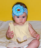 Portrait of a beautiful little baby girl in a yellow dress with a bow on her head that plays beads jewelry around his neck Stock Images