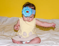 Portrait of a beautiful little baby girl in a yellow dress with a bow on her head that plays beads jewelry around his neck Stock Photo