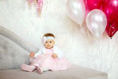 Portrait of a beautiful little baby. Portrait of a beautiful little baby in pink dress sitting on sofa with balls. Happy birthday royalty free stock photos