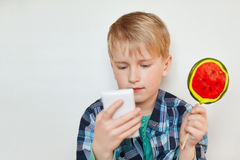Portrait of beautiful little boy licking lollipop having concentrated look while using mobile phone reading e-book or playing vide. O games online resting at Royalty Free Stock Image