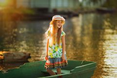 Portrait of a beautiful little girl in a boat at sunset on the lake Stock Image