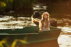 Portrait of a beautiful little girl in a boat at sunset on the lake Stock Photo