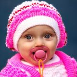 Portrait of a beautiful little girl (child). She wore a bright knitted suit and hat. Color suit white and pink Royalty Free Stock Images