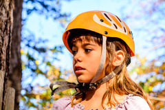 Portrait of a beautiful little girl. Little girl is climbing in adventure park Stock Photos