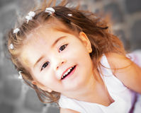 Portrait of a beautiful little girl close-up. Portrait of a happy young little girl smiling under the sunlight Stock Images