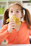 Portrait of a beautiful little girl eating a banana Stock Photography